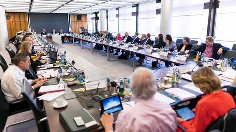 Mitglieder des Rundfunkrats sitzen in einem Konferenzraum um einen großen Konferenztisch herum