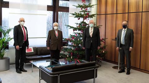 Berthold Trischler, Dr. Christean Wagner, Armin Clauss und Manfred Krupp tragen Mundschutz und stehen mit deutlichem Abstand zueinander in einem Foyer.