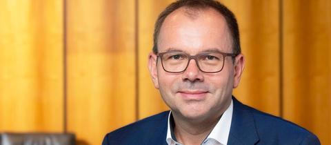 Mathias Wagner, Mitglied des Rundfunkrats, im Hintergrund eine holzvertäfelte Wand